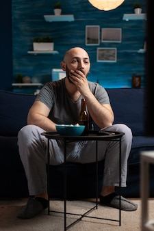 Focused concentrated man watching interesting movie show on television. male sitting on comfortable sofa dressed in pajama late at night in living room having shocked expression