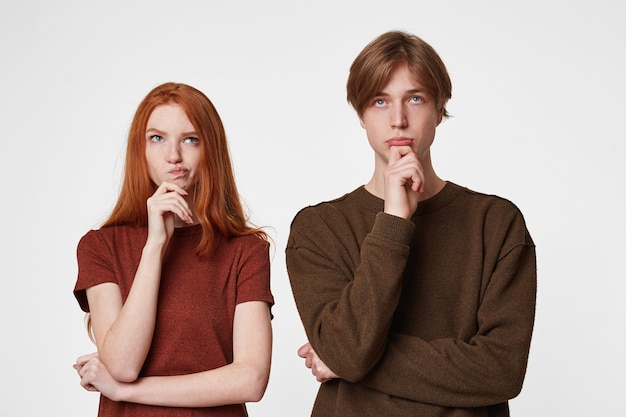 Focused concentrated young couple keep arm on chin and look thoughtfully up