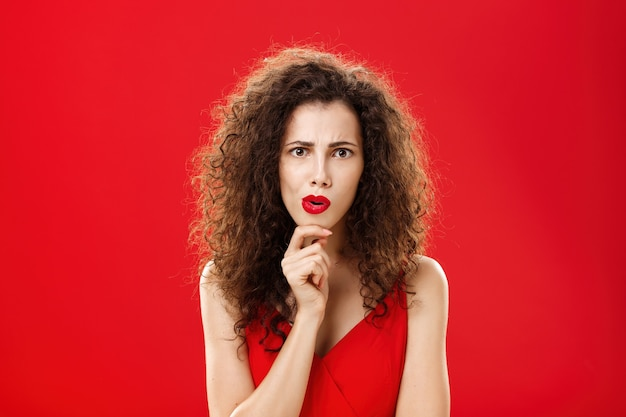 Focused and concerned shocked gossip girl with curly hairstyle frowning folding lips rubbing chin looking strict and determined at camera while thinking or listening carefully to shocking speech.