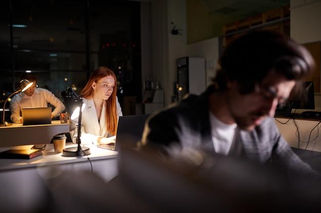 마감일을 완료하려고 비즈니스 보고서를 확인 자신감 빨간 머리 여성 회사원 집중. 밤에 초과 근무를하는 직장에 앉아있는 laptpop 화면에서 통계를 보는 사업가