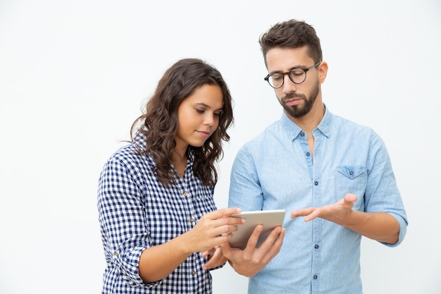 Focused couple using tablet pc