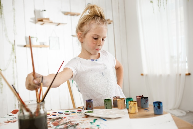 Focused on creative process cute little blond with hair bun and freckled face in white t-shirt in art room.
