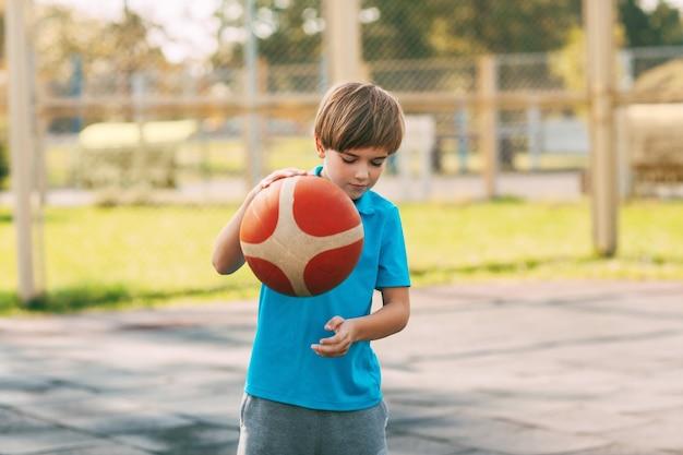 焦点を当てたかわいい男の子のアスリートは、バスケットボールのゲームでボールをリードします。放課後、男の子がバスケットボールをする