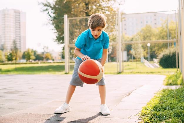 焦点を当てたかわいい男の子のアスリートは、バスケットボールのゲームでボールをリードします。