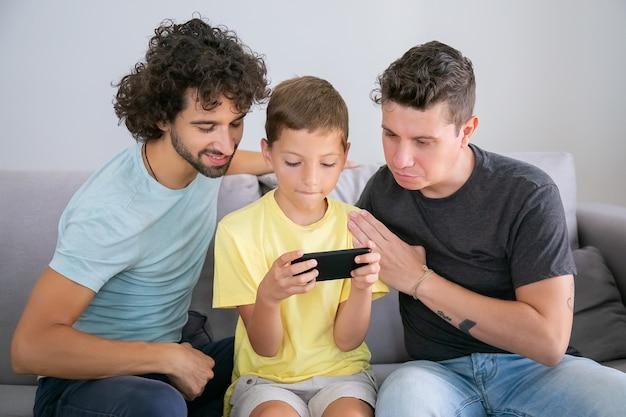 スマートフォンを使って焦点を合わせたかわいい男の子、彼の2人のお父さんは彼のそばに座って画面を見ています。正面図。家族とコミュニケーションの概念