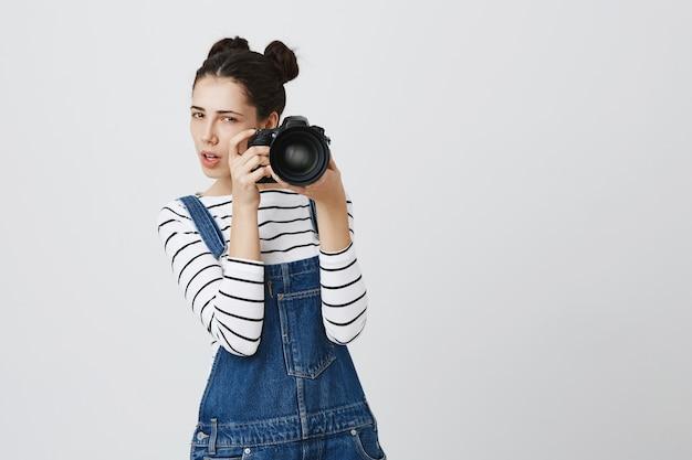 Сосредоточенная милая девушка-фотограф фотографирует на камеру, задумчиво глядя на свою модель