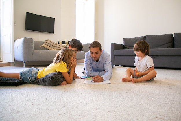Focused dad and kids lying on carpet and painting on paper. loving caucasian father drawing with markers and playing with cute children at home. childhood, game activity and fatherhood concept