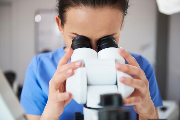 Сосредоточенный стоматолог смотрит в микроскоп
