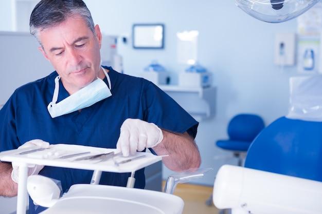 Focused dentist picking up tool