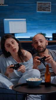 Сосредоточенная решительная пара, играющая в видеоигру поздно ночью, сосредоточенно пытается выиграть онлайн-соревнование