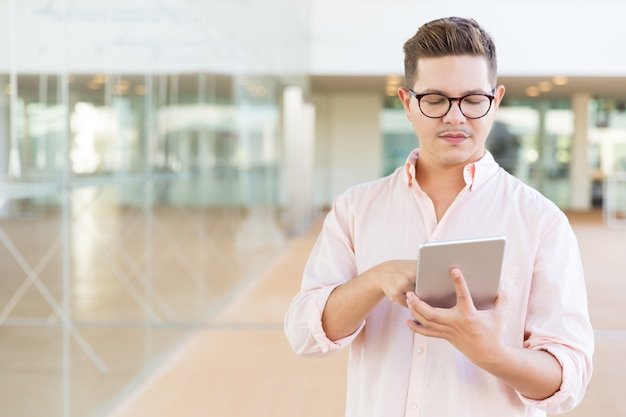 Focused developer standing in hallway and working on tablet