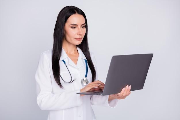 Сосредоточенные доктор девушка просматривает информацию в ноутбуке на сером фоне