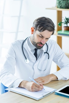 Focused doctor making notes in office