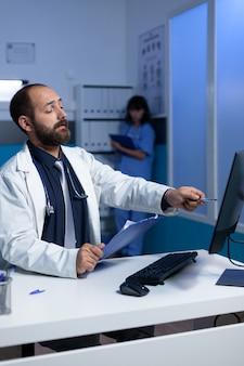 Medico concentrato che punta al computer per il lavoro di analisi di notte