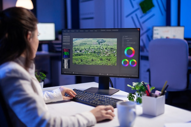 Focused editor retoucher editing color grade on professional computer
