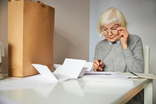 Сосредоточенная пожилая белокурая кавказская дама в очках смотрит на счета за коммунальные услуги на столе Premium Фотографии