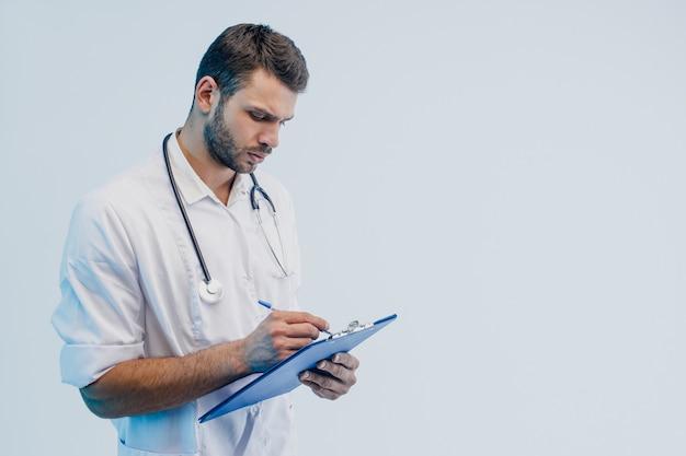 Сосредоточенный европейский мужской доктор писать что-то в буфере обмена. молодой бородатый мужчина со стетоскопом и в белом халате. изолированные на сером фоне с бирюзовым светом. студийная съемка. скопируйте пространство.