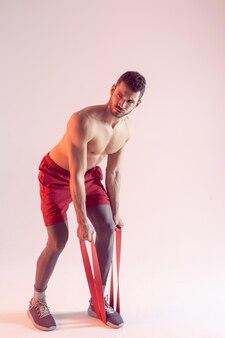 Сосредоточенный европейский спортсмен делает упражнения с лентой сопротивления. молодой красивый мускулистый бородатый мужчина с обнаженным спортивным торсом. изолированные на бежевом фоне. студийная съемка. копировать пространство