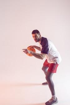 집중된 유럽 스포츠맨은 농구를 하고 손가락으로 가리킵니다. 젊고 잘생긴 수염이 있는 농구 선수는 운동복을 입는다. 베이지색 배경에 고립. 스튜디오 촬영. 복사 공간