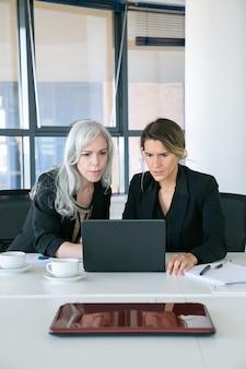 オフィスでコーヒーを飲みながらテーブルに座ってノートパソコンのディスプレイを見ている興奮したビジネスウーマンに焦点を当てた。正面図。チームワークとコミュニケーションの概念