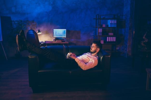 焦点を当てたエグゼクティブの男は黒いソファの夜のオフィスにうそをつく