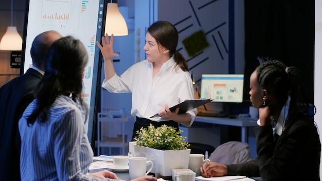 사무실 회의실에서 초과 근무를 하는 프레젠테이션 모니터를 사용하여 회사 솔루션을 제시하는 집중된 경영진입니다. 저녁에 재무 통계를 분석하는 다양한 다민족 팀워크