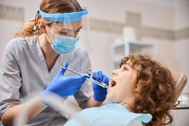 보호 장비를 착용하고 아이에게 마취 주사를주는 집중된 공정한 머리 치과 의사