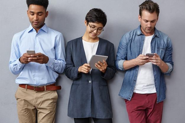 Concentrati giovani alla moda di diverse nazioni, leggono attentamente le informazioni su tablet e smartphone
