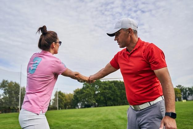 골프 전문가로부터 클럽을 스윙하는 방법을 배우는 선글라스에 집중된 여성 초보자