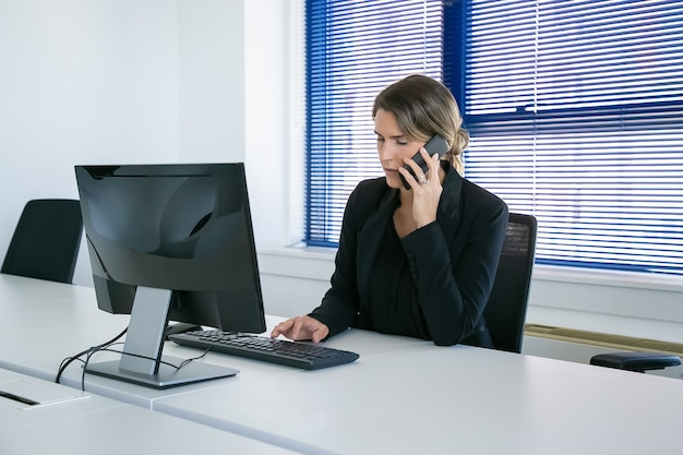 オフィスの職場でコンピューターを使用しながら携帯電話で話しているスーツの女性ビジネスリーダーに焦点を当てた。ミディアムショット。デジタル通信とマルチタスクの概念