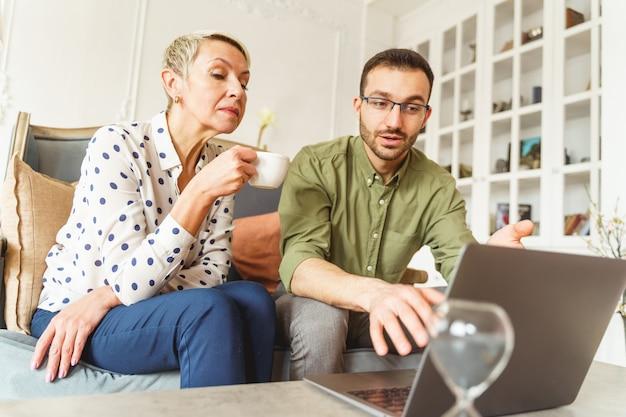 전문 점성가 옆에 앉아 손에 컵을 들고 집중된 여성 고객