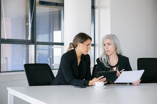 Целенаправленные коллеги-женщины обсуждают и анализируют отчеты. два профессионала сидят вместе, держат документы, используют планшет и разговаривают. концепция совместной работы