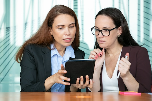 Focused female colleagues watching content on tablet together, looking at screen in excitement while sitting at table in meeting room.