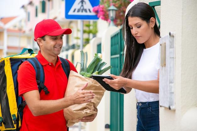 소포를 받기 위해 서명하는 여성 고객에 집중했습니다. 음식과 함께 패키지를 배달하는 제복의 긍정적 인 택배. 배송 또는 배달 서비스 개념
