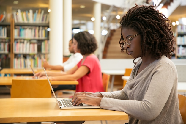 Focused female customer using public wi-fi hotspot in library
