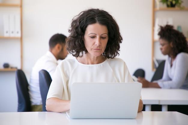 Сосредоточенный женский работник работает на ноутбуке в офисе