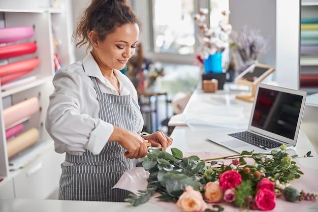Focused female flower shop worker cutting off flower stems