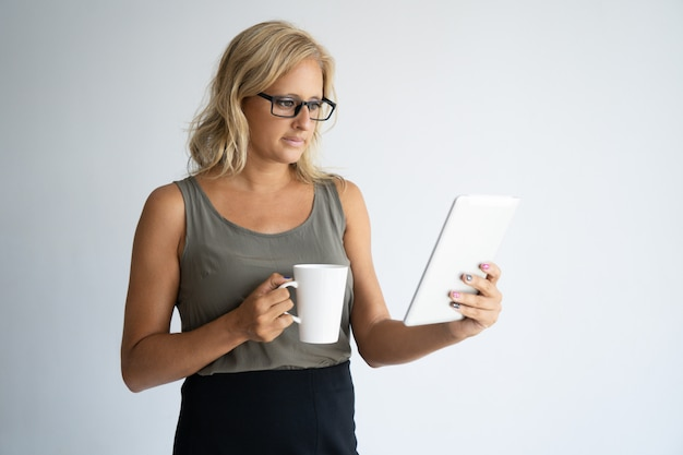 Focused female freelancer drinking coffee and checking email.