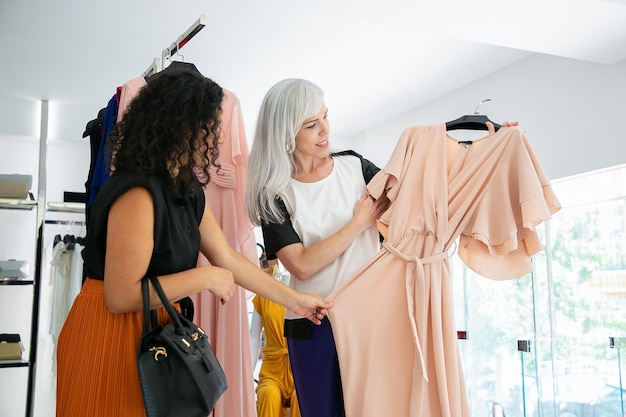 Focused female friends choosing new clothes in fashion store together, holding and looking over party dress with hanger. consumerism or shopping concept