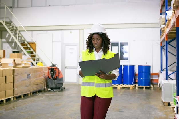 Focused female logistic employee in hardhat and safety vest walking in warehouse, carrying open folder, looking through document. copy space, front view. labor and inspection concept