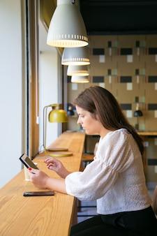Responsabile femminile concentrato utilizzando tablet mentre è seduto alla scrivania in uno spazio di co-working o caffetteria