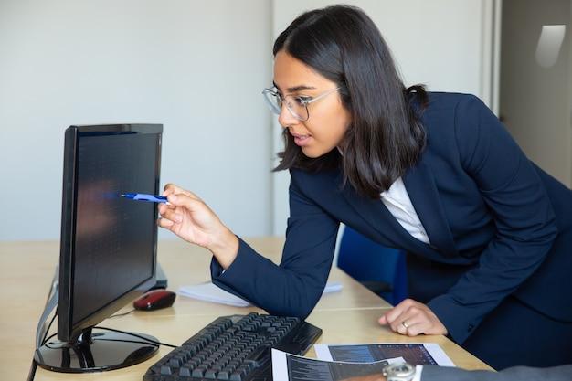 금융 차트와 사무실 테이블에 기울고 모니터에 통계 보고서에서 여성 전문 포인팅 펜을 집중. 미디엄 샷. 재정 고문 개념