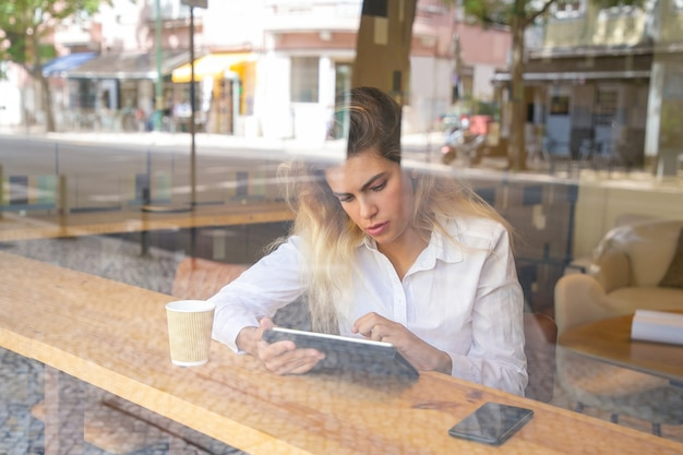 Focused female professional sitting at desk in co-working space or coffee shop, using tablet