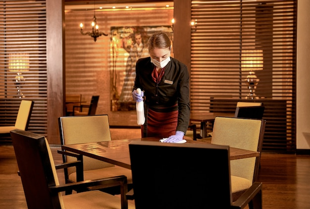 Focused female restaurant employee tidying up a table