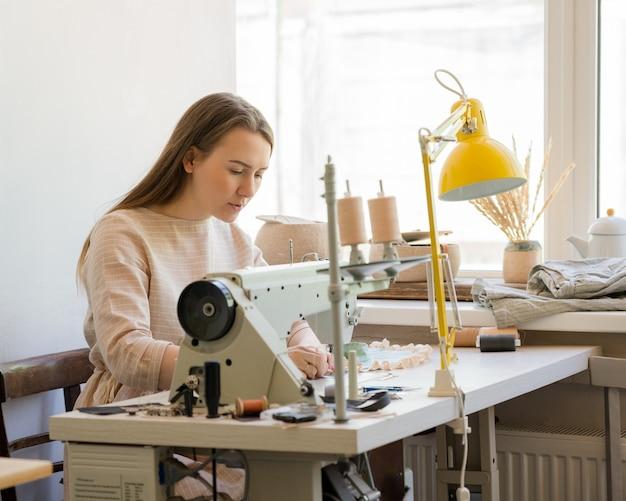 Специализированная швея-женщина шьет одежду на своем рабочем месте