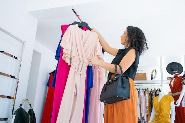 Сосредоточенная женщина-покупательница выбирает вешалку с вечерним платьем из стойки для попытки. женщина выбирает ткань в магазине модной одежды. потребительство или розничная концепция