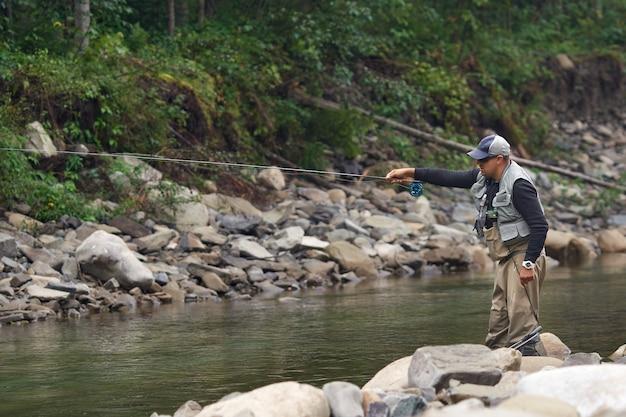 Сосредоточенный рыбак стоит в реке и ждет ловли рыбы на крючке. человек в повседневной одежде проводит свободное время для спокойной деятельности в горах.