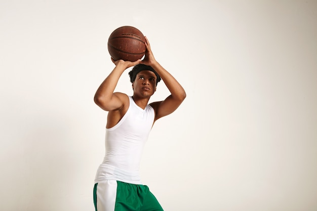 Сосредоточенный молодой афроамериканский игрок в бело-зеленой баскетбольной экипировке, бросающий старинный баскетбольный мяч на белом