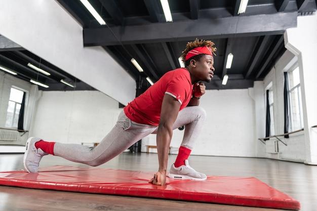 快適な衣装を着て赤いマットの上で広いスクワットを作る集中フィットの若い男