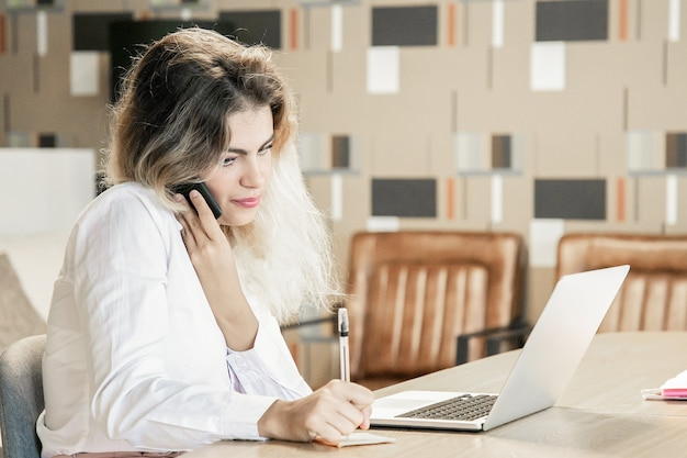 Focused freelancer discussing project with customer on phone